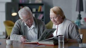 Le coppie felici anziane spendono insieme il tempo ed il nostalgico essi che sembrano vecchio album di foto e sorridere video d archivio