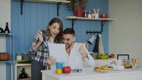 Le coppie felici attraenti ricevono la lettera di spiegamento di buone notizie nella cucina mentre abbia prima colazione a casa immagine stock