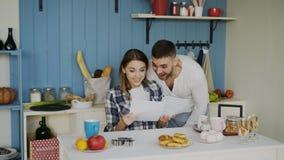 Le coppie felici attraenti ricevono la lettera di spiegamento di buone notizie nella cucina mentre abbia prima colazione a casa immagini stock