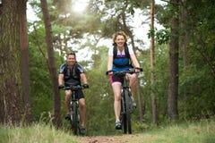 Le coppie felici che godono di una bici guidano all'aperto Fotografia Stock