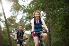Le coppie felici che godono di una bici guidano in natura Fotografia Stock