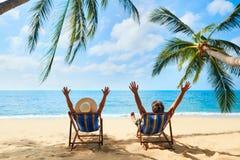 Le coppie felici con le armi su si rilassano sulla spiaggia godono di bello mare sull'isola tropicale fotografia stock