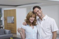 Le coppie felici con digitano la nuova casa immagini stock