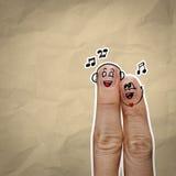 Le coppie felici del dito nell'amore con lo smiley dipinto e cantano una s Fotografia Stock Libera da Diritti