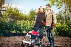 Le coppie felici di una famiglia degli agricoltori sul loro giardino si rallegrano su una pianta Fotografie Stock Libere da Diritti