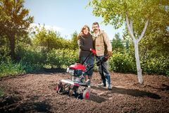Le coppie felici di una famiglia degli agricoltori sul loro giardino si rallegrano sulla a Immagine Stock