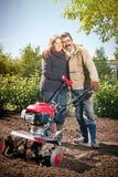 Le coppie felici di una famiglia degli agricoltori sul loro giardino si rallegrano sulla a Immagini Stock Libere da Diritti