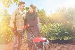 Le coppie felici di una famiglia degli agricoltori sul loro giardino si rallegrano sulla a Fotografia Stock