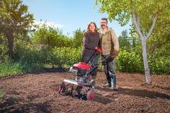 Le coppie felici di una famiglia degli agricoltori sul loro giardino si rallegrano sulla a Fotografie Stock