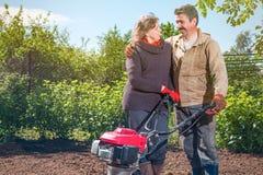 Le coppie felici di una famiglia degli agricoltori sul loro giardino si rallegrano sulla a Immagine Stock Libera da Diritti