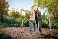 Le coppie felici di una famiglia degli agricoltori sul loro giardino si rallegrano sulla a Immagini Stock