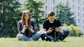 Le coppie felici giocano il gioco mobile sullo smartphone, sedentesi sull'erba nel parco L'uomo vince il gioco, donna persa video d archivio