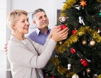 Le coppie felici mature decorano l'abete per le feste del Natale fotografia stock