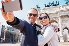 Le coppie felici prendono una foto del selfie sull'arco di pace a Milano Fotografia Stock