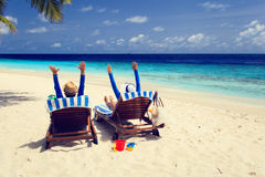 Le coppie felici si rilassano su una spiaggia tropicale Immagine Stock