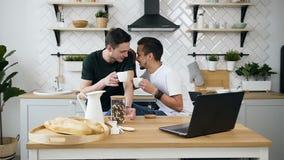 Le coppie gay allegre degli uomini bei stanno sedendo dietro il tavolo da cucina qualcosa che parlano per durante il caffè bevent stock footage