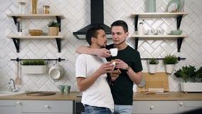 Le coppie gay belle sono abbraccianti e beventi il caffè Concetto gay di relazioni Giovani coppie gay maschii che si abbracciano archivi video
