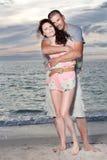 Le coppie godono del giorno di estate alla spiaggia. Fotografie Stock