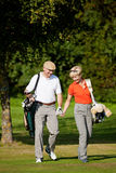 le coppie golf il gioco maturo fotografia stock