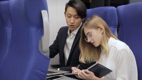 Le coppie i colleghi multiethnical stanno preparando per la presentazione di affari mentre viaggiavano in treno archivi video