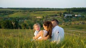Le coppie incinte con la figlia del bambino fanno il tempo libero appoggiare all'aperto la vista fotografia stock libera da diritti