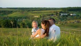 Le coppie incinte con la figlia del bambino fanno il tempo libero appoggiare all'aperto la vista video d archivio