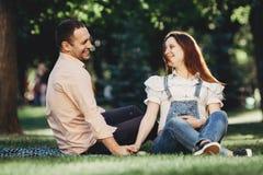 Le coppie incinte felici godono insieme del tempo fotografia stock
