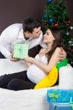 Le coppie incinte felici si avvicinano all'albero di Natale Immagine Stock