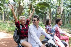 Le coppie libere felici che conducono il motorino godono del viaggio in Forest Cheerful Friends Road Trip tropicale fotografia stock