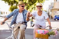 Le coppie mature felici che vanno per una bici guidano nella città Fotografie Stock Libere da Diritti