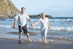 Le coppie mature senior adorabili sul loro 60s o 70s si sono ritirate la camminata felice e rilassata sulla riva di mare della sp Immagini Stock Libere da Diritti