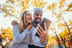 Le coppie miste che camminano in autunno parcheggiano, facendo uso della linguetta digitale immagine stock