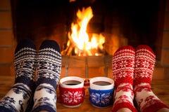 Le coppie nei calzini di Natale si avvicinano al camino immagine stock