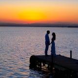 Le coppie nell'amore appoggiano la siluetta chiara nel lago Fotografia Stock Libera da Diritti