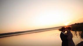 Le coppie nell'amore appoggiano la siluetta leggera al tramonto dell'arancia del lago stock footage