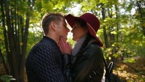 Le coppie nell'amore baciato in autunno parcheggiano al tramonto, rallentatore stock footage