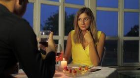 Le coppie nell'amore cenando dal lume di candela, bevono il vino rosso e la conversazione divertente archivi video