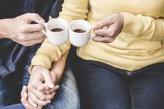 Le coppie nell'amore che si tiene per mano con il caffè amano sulla tavola, il tono d'annata Fotografie Stock Libere da Diritti