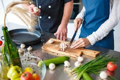 Le coppie nell'amore, passano insieme il tempo nella cucina che cucina qualcosa, la ragazza tagliano i funghi Fotografia Stock