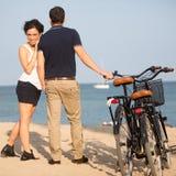 Le coppie nell'amore sulla città tirano con le bici Immagine Stock