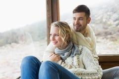 Le coppie nell'inverno indossano lo sguardo fuori attraverso la finestra di cabina Fotografia Stock