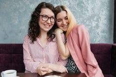 Le coppie omosessuali di giovani amiche attraenti delle donne nell'amore stanno bevendo il caffè ed abbracciare fotografie stock