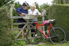 Le coppie pensionate su un ciclo guidano la lettura della loro mappa immagine stock