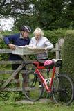 Le coppie pensionate su un ciclo guidano la lettura della loro mappa Fotografia Stock Libera da Diritti