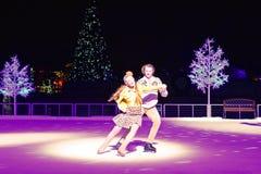 Le coppie piacevoli che pattinano sul ghiaccio al Natale mostrano nell'area internazionale dell'azionamento immagini stock libere da diritti
