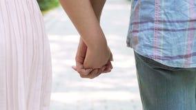 Le coppie romantiche alla data che cammina con le mani hanno collegato, fiducia reciproca, primo piano stock footage