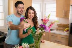 Le coppie romantiche nell'amore hanno un mazzo dei fiori e della felicità della parte ad una data Fotografia Stock