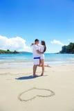 Le coppie romantiche nell'amore si divertono sulla spiaggia con il drawi del cuore fotografie stock