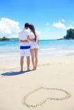 Le coppie romantiche nell'amore si divertono sulla spiaggia con il drawi del cuore immagini stock libere da diritti