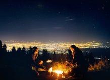Le coppie romantiche si avvicinano al fuoco di accampamento alla notte stellata fotografie stock